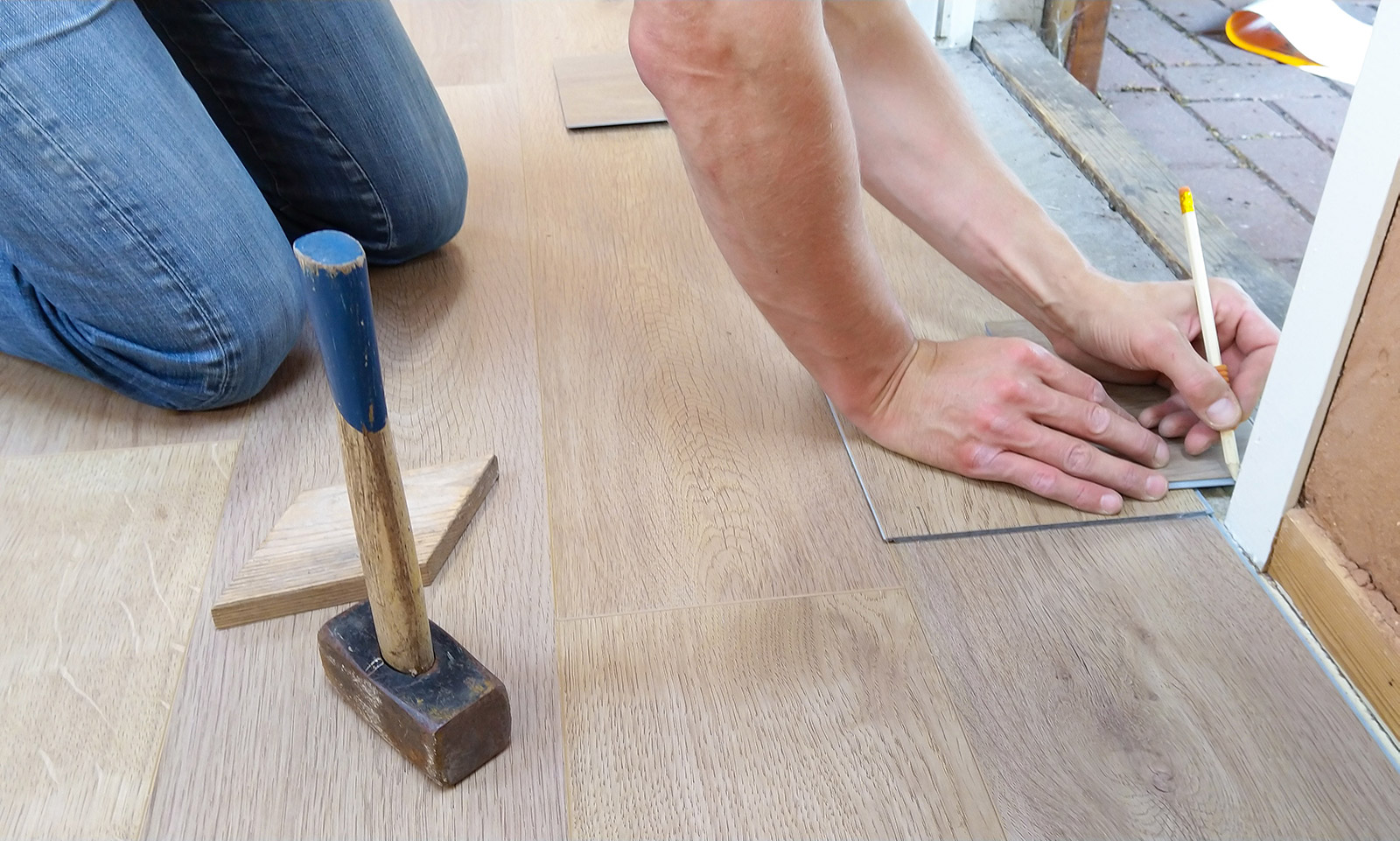 man measuring floor tile sizes