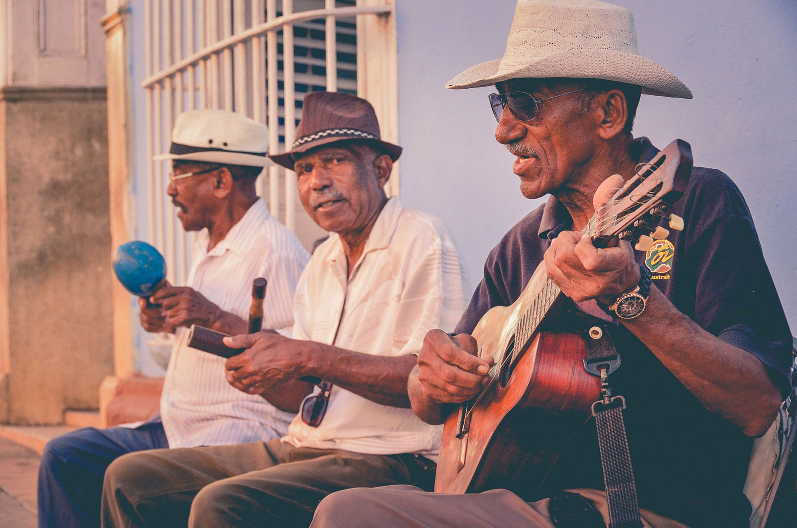 three older adults playing guitars