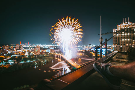 man viewing fireworks in a city from the roof