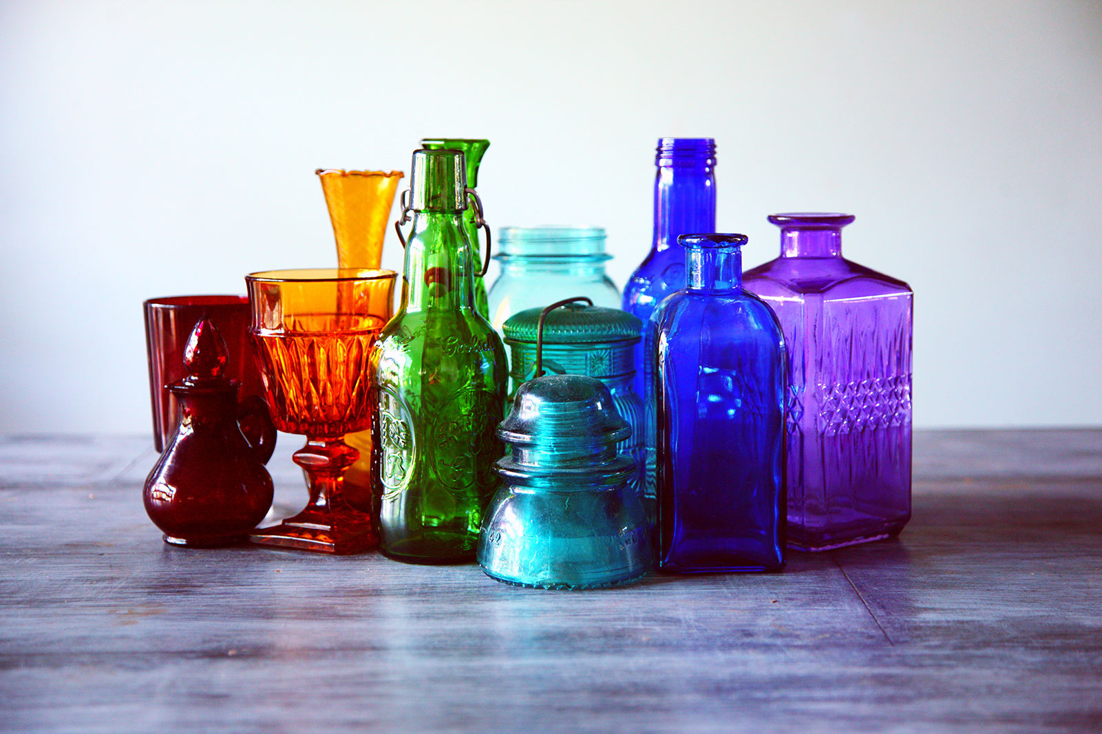 a group of colored glass jars and containers