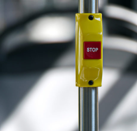 a stop button on a bus rail