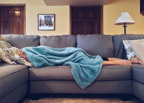 man lying on couch with blanket over head sick