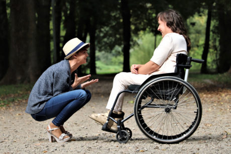 woman in wheelchair speaking with man
