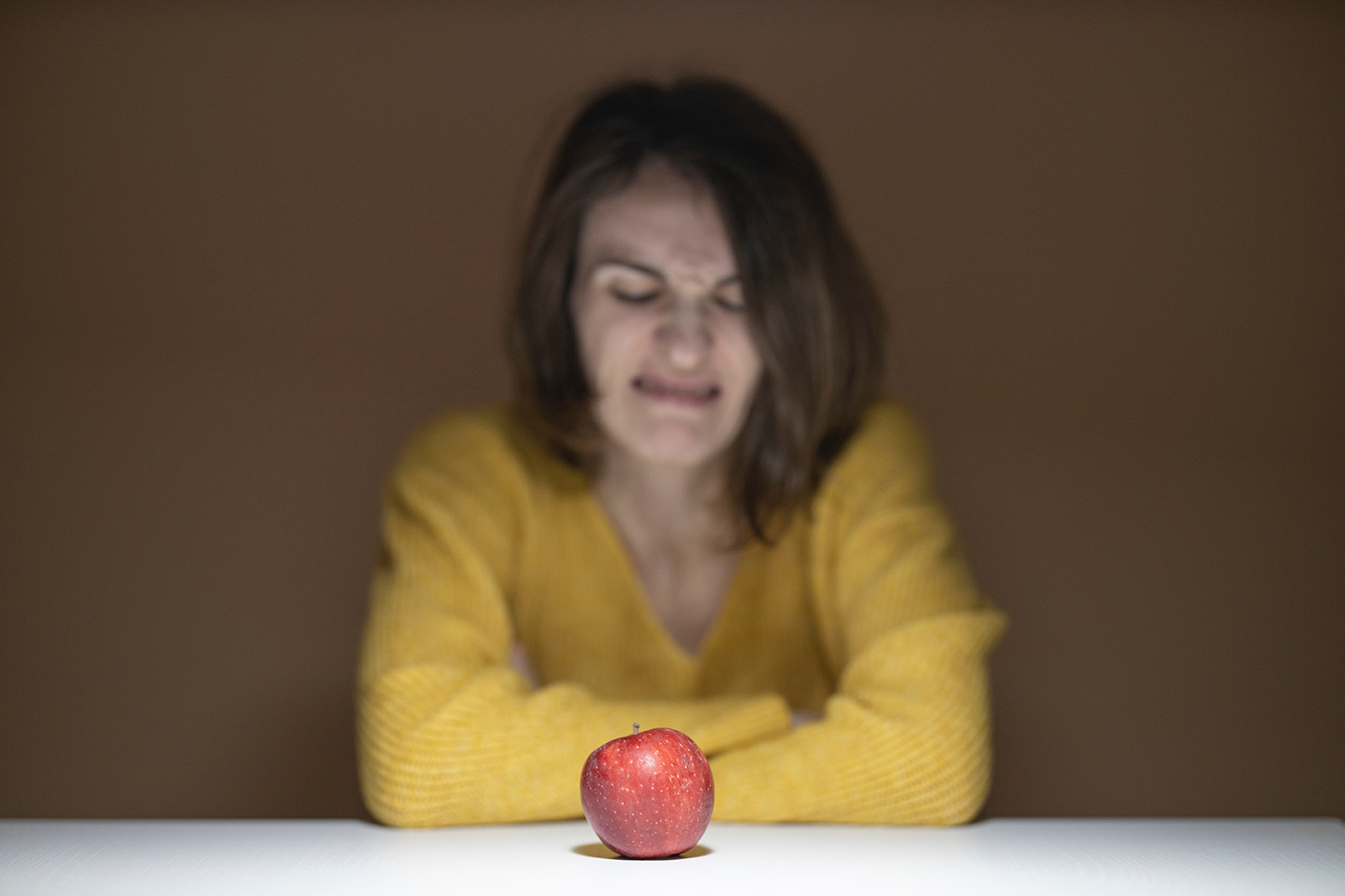 woman disgusted looking at apple