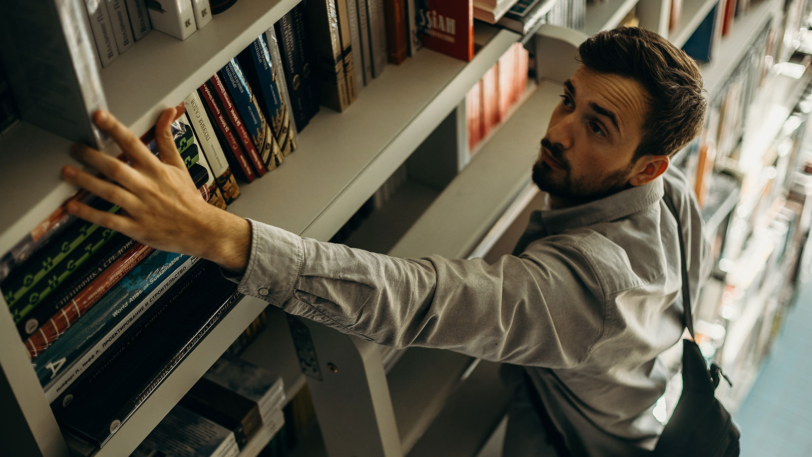 man reaching for a book